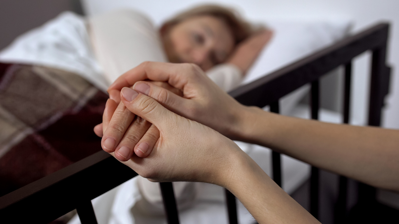 Daughter supporting mother lying on hospital bed